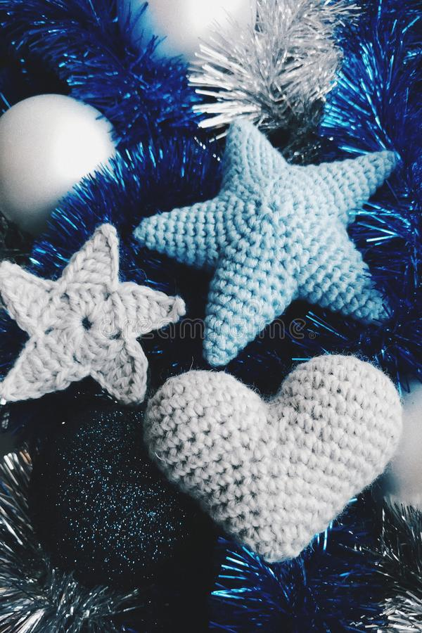 Knitted stars, heart and Christmas balls are on the blue and silver garlands royalty free stock photo