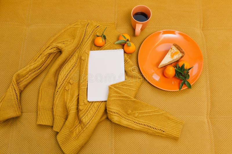 Knitted sweater, cup of coffee, cheesecake, mandarines, notebook on orange background from above. stock images