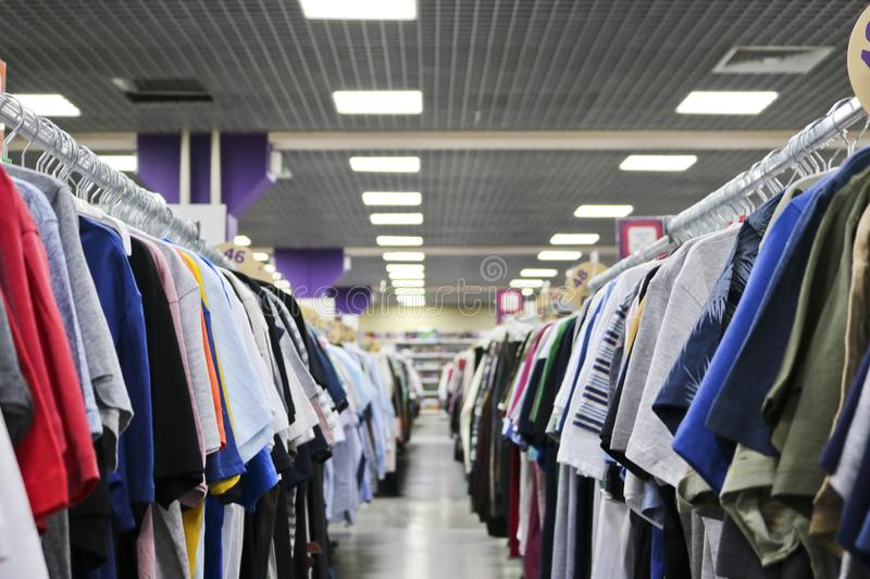 Knitted T-shirts hanging in two rows on hangers in the store blurred. On the eve of Black Friday. royalty free stock image
