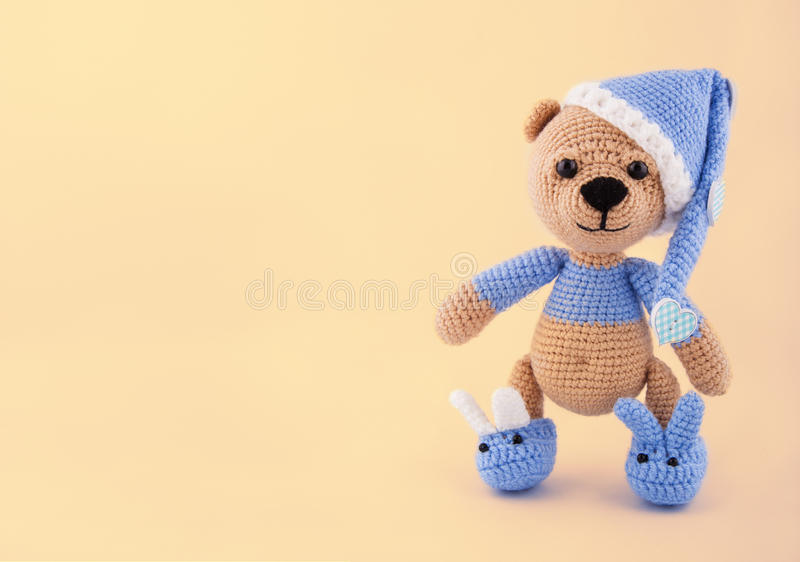 Knitted teddy bear in a cap and slippers on a gentle yellow background. Toys made by hand. A soft gift. Copy space royalty free stock photos