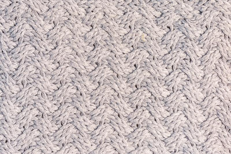 Knitted texture with an unusual pattern close-up. Wool fabric. Gray background for layouts. stock image
