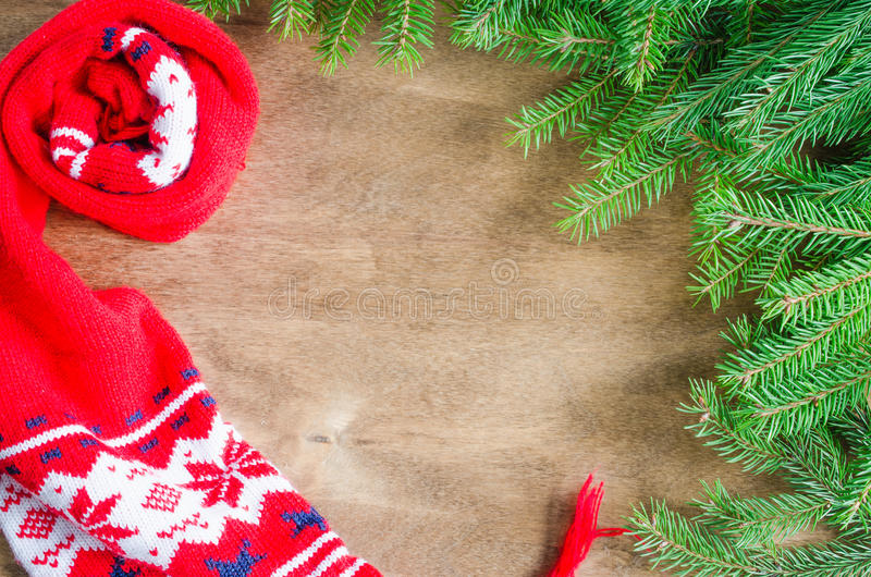 Knitted warm winter scarf and branch fir tree on rustic wooden background with copy space. Christmas background. Top view stock images