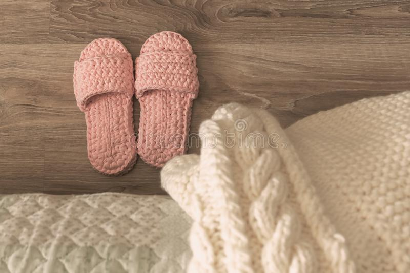 Knitted white bedspread and Slippers near the bed.  stock image