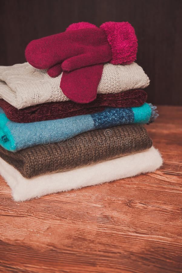 Knitted, winter sweaters and warm mittens on a wooden background. stock images