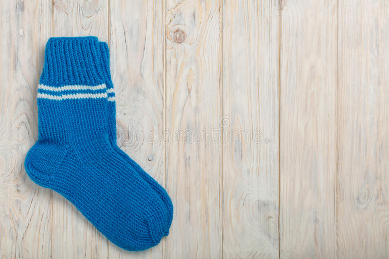 Knitted wool socks blue color on light wooden background. Selective focus royalty free stock photo