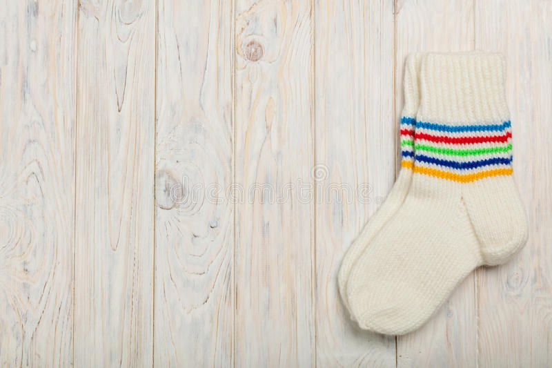 Knitted wool socks white color on bright wooden background. stock images