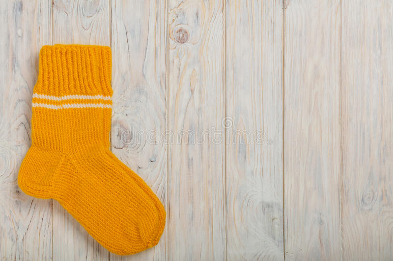 Knitted wool socks yellow color on light wooden background. Selective focus royalty free stock images