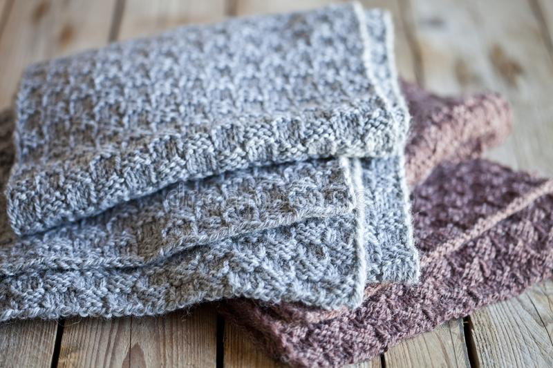 Knitted woolen grey and brown scarves. On wooden background stock images