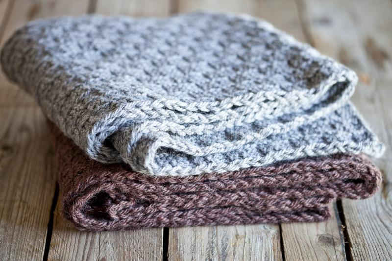 Knitted woolen grey and brown scarves. On wooden background royalty free stock image