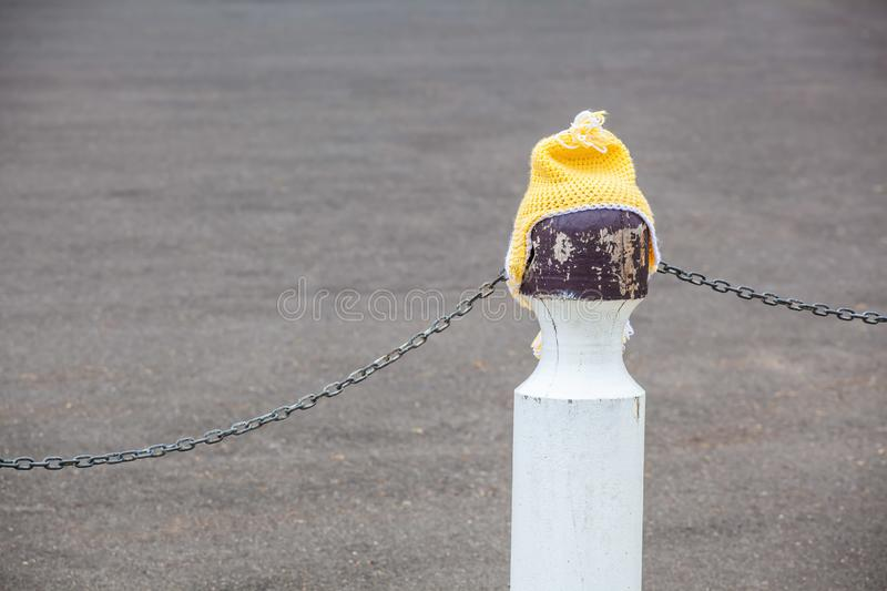 Knitted yellow beanie on a pole. Knitted yellow beanie on a pole with copy space stock images