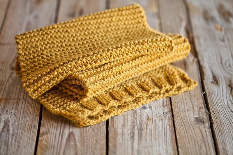 Knitted yellow scarf. On wooden background stock photography