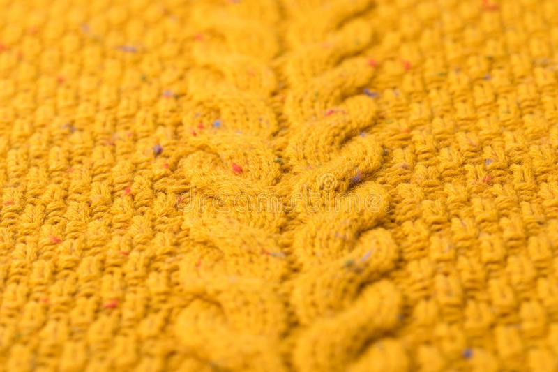 Knitted yellow sweater with pattern. Texture of warm knitted yellow sweater with pattern royalty free stock image