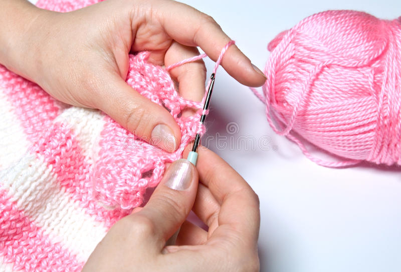 Knitting. The woman knits a pink jacket royalty free stock photography