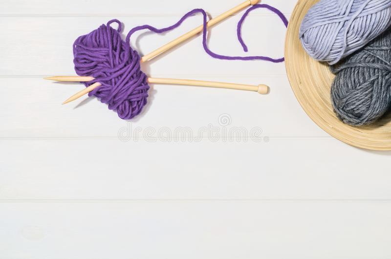 Knitting accessories top view on white wooden background stock photography