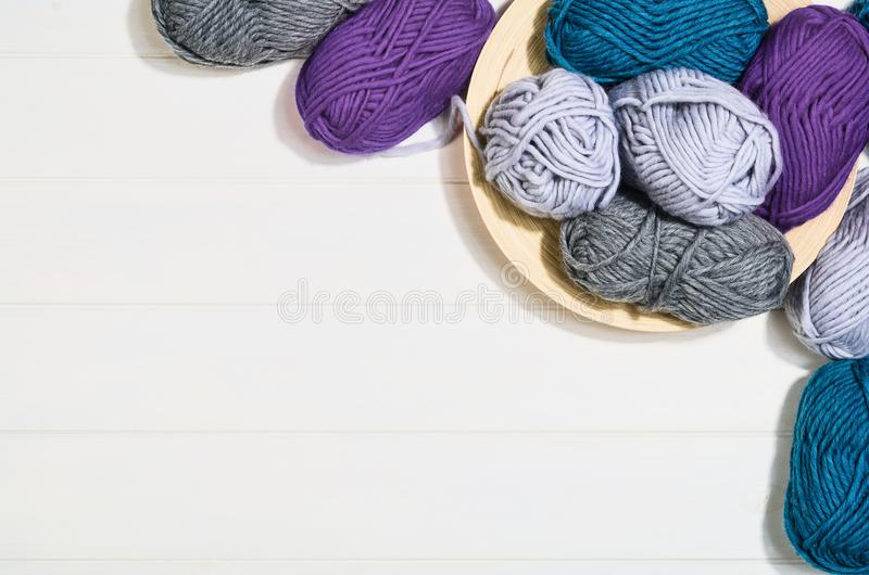 Knitting accessories top view on white wooden background stock photos