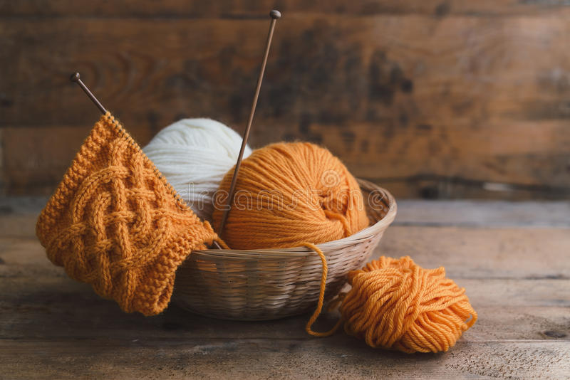 Knitting. Balls of yarn in basket with knitting needles stock photography