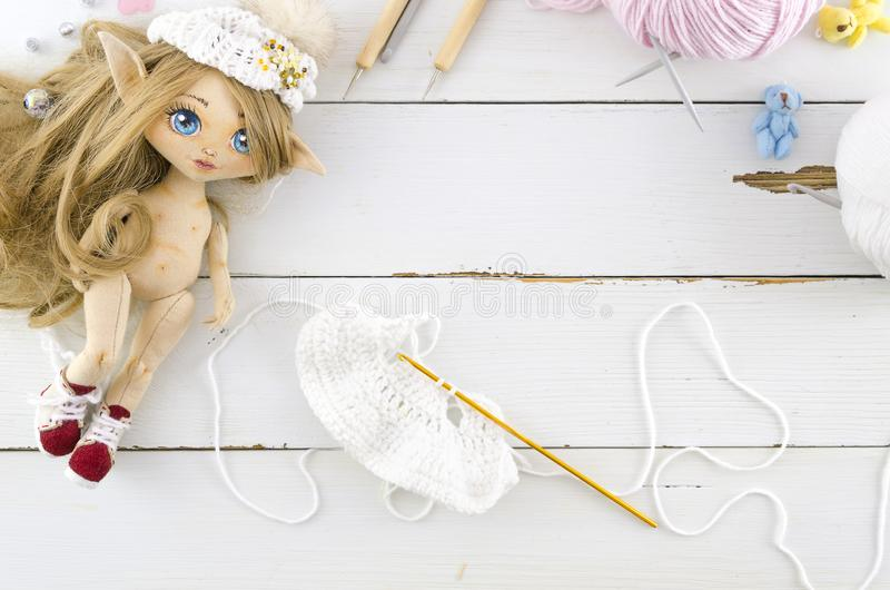 Knitting clothes and toy dress for a doll. Flat lay work in progress royalty free stock photos