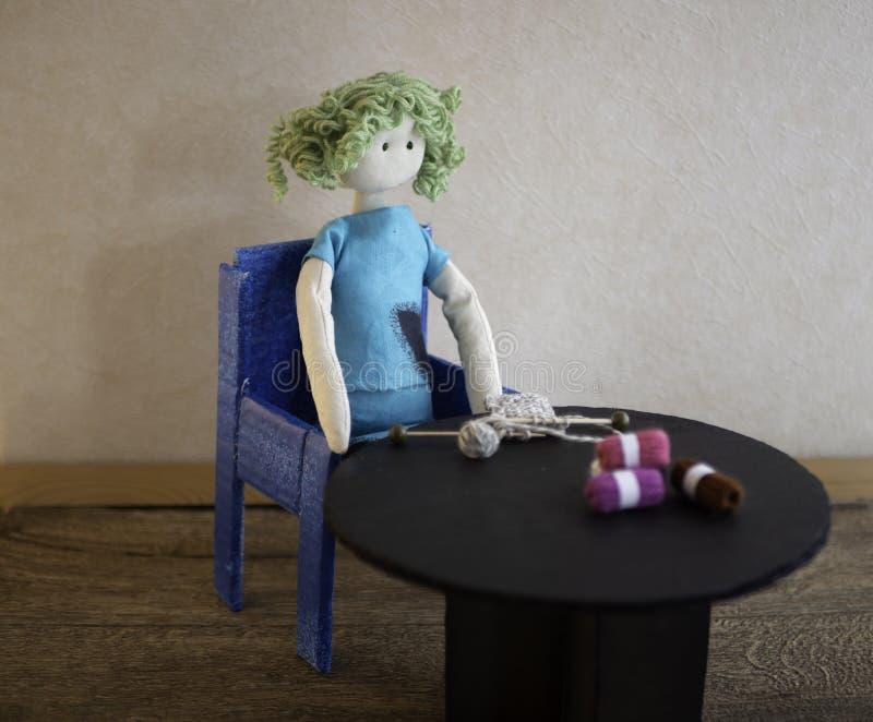 Knitting doll at a table stock photo