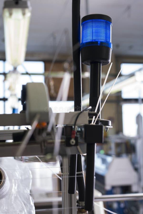 Knitting machine blue signal lamp shot. Automatic knitting machine blue signal lamp view stock photo