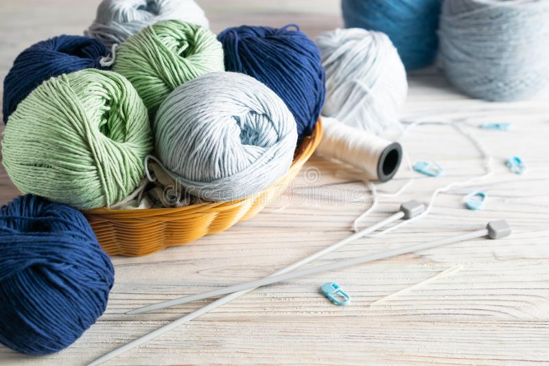 Knitting materials. Blue and green yarn in a basket with needles on white wooden table stock images