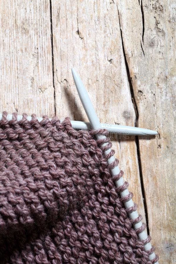 Knitting and needles. Brown scarf closeup on wooden background royalty free stock photos