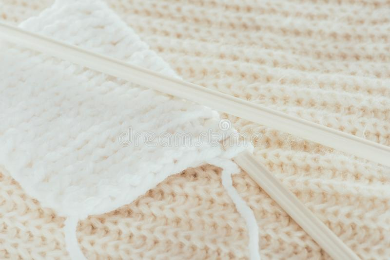 Knitting needles with white woolen yarn. Close up of knitting needles with white woolen yarn royalty free stock photography