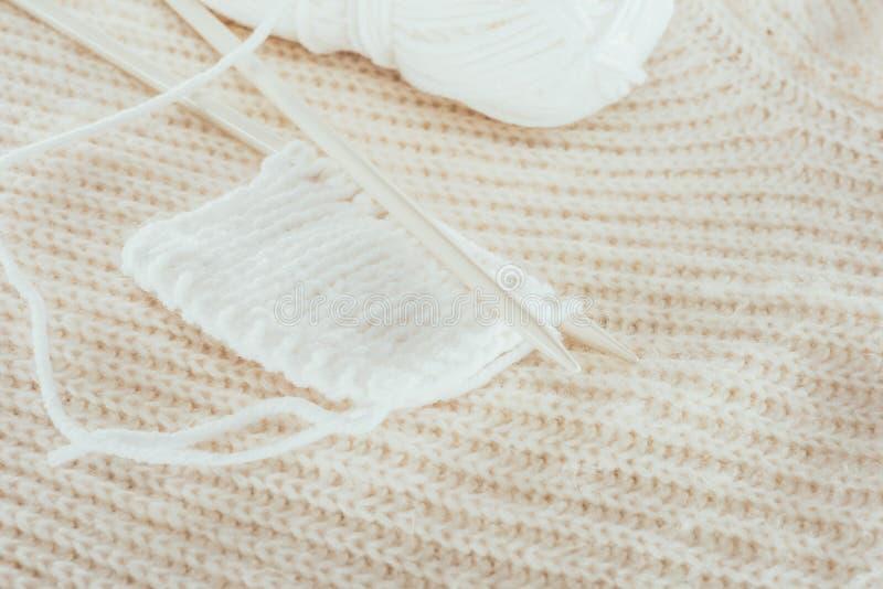 Knitting needles with white woolen yarn. Close up of knitting needles with white woolen yarn royalty free stock photo