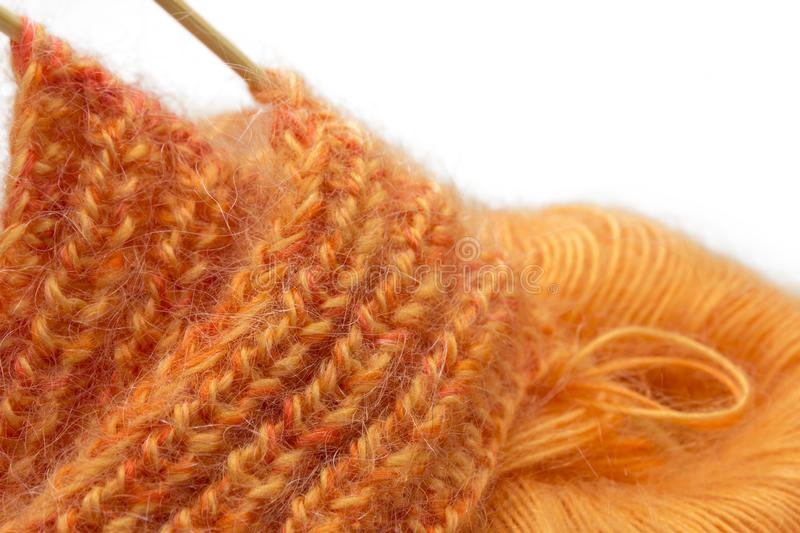 Knitting orange colorful melange mohair wool ball and knitting needles isolated on white background. The beginning of comfort knit. Cloth. Place for text royalty free stock image