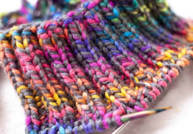 Knitting pattern texture, colorful yarn and needles close-up stock image