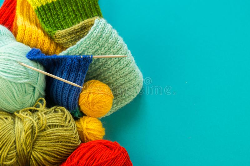 Knitting a rainbow scarf and hat Blue background royalty free stock images