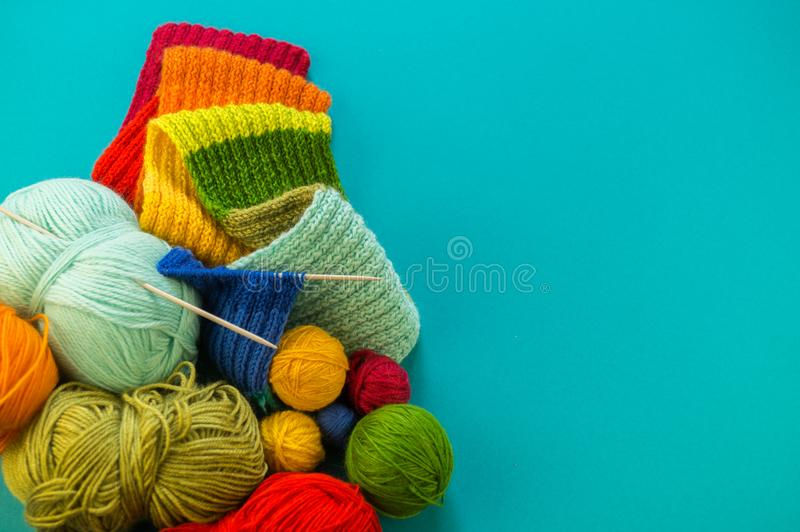 Knitting a rainbow scarf and hat Blue background stock photography
