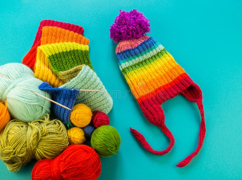 Knitting a rainbow scarf and hat Blue background stock photos