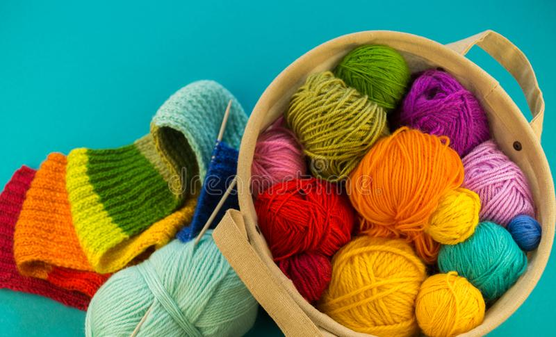 Knitting a rainbow scarf and hat Blue background royalty free stock photos
