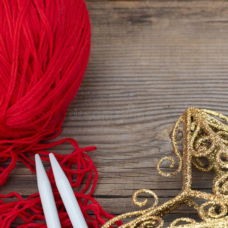 Knitting sticks red yarn and yellow christmas decoration on old textured wooden background. Square with copy space. Clew royalty free stock image
