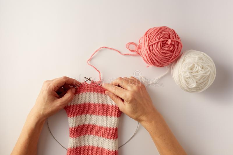 Knitting stripes with two colors of yarn. stock photo