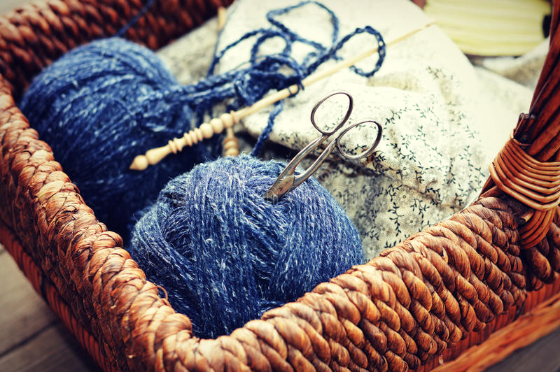Knitting Supplies. A brown basket filled with blue yarn, knitting needles fabric and some silver sewing scissors stock photography