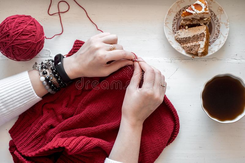 All for needlework: red thread, knitting, knitting needles on a wooden gray table. Top view. lose-up. Copy space royalty free stock photography