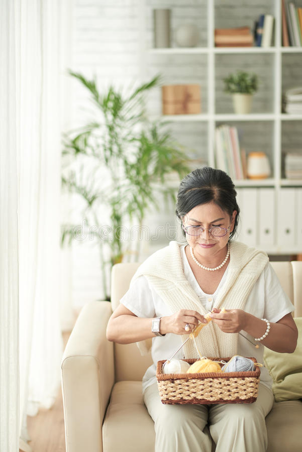 Knitting woman. Pretty aged Asian woman knitting at home royalty free stock photo