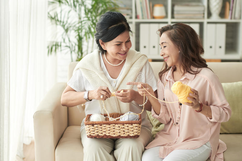 Knitting women. Senior Vietnamese female friends knitting together and chatting royalty free stock image