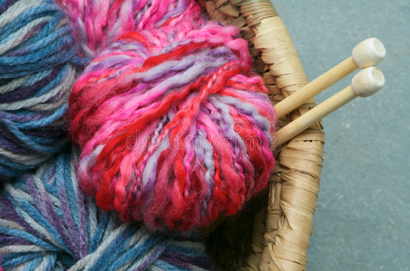 Knitting wool. Pretty pink and blue yarn with knitting needles in rattan basket
