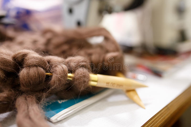 Knitting with wool thick soft brown color yarn on the needles.  stock images