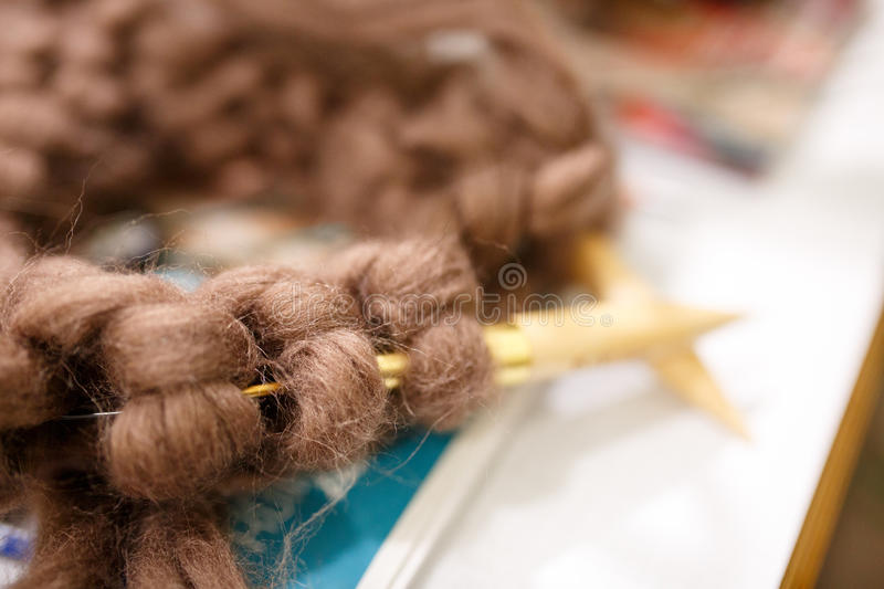 Knitting with wool thick soft brown color yarn on the needles.  stock image