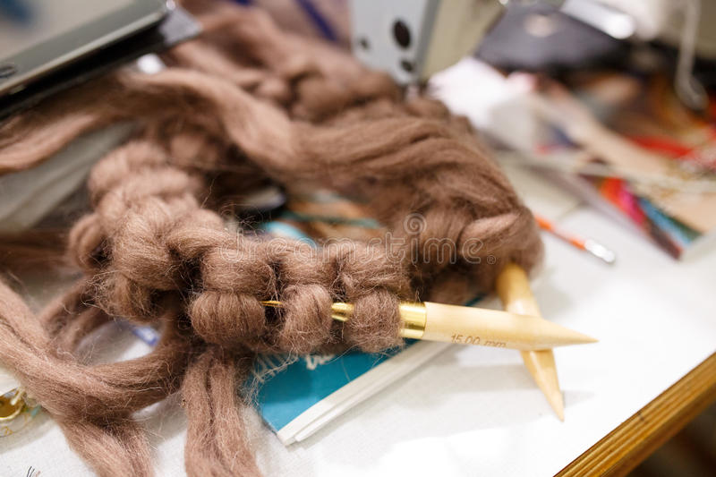 Knitting with wool thick soft brown color yarn on the needles.  stock photos
