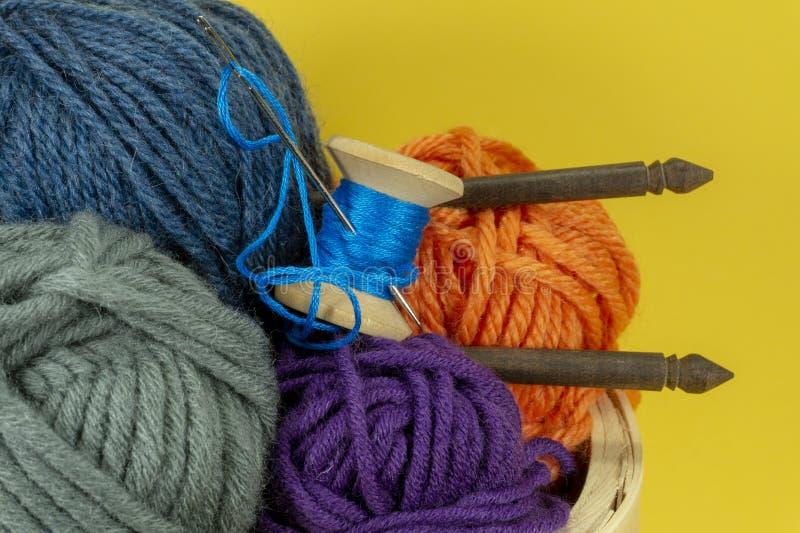 Knitting yarn balls and needles in basket stock photos