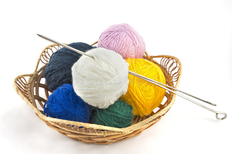 Knitting yarn balls and needles in basket on a white background royalty free stock photography