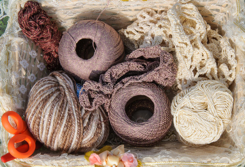 Knitting yarn in basket on green grass stock images