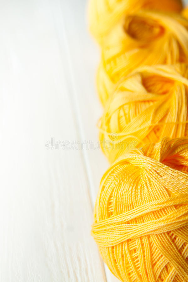 Knitting yarn rolled into balls. On a white wooden background stock photography