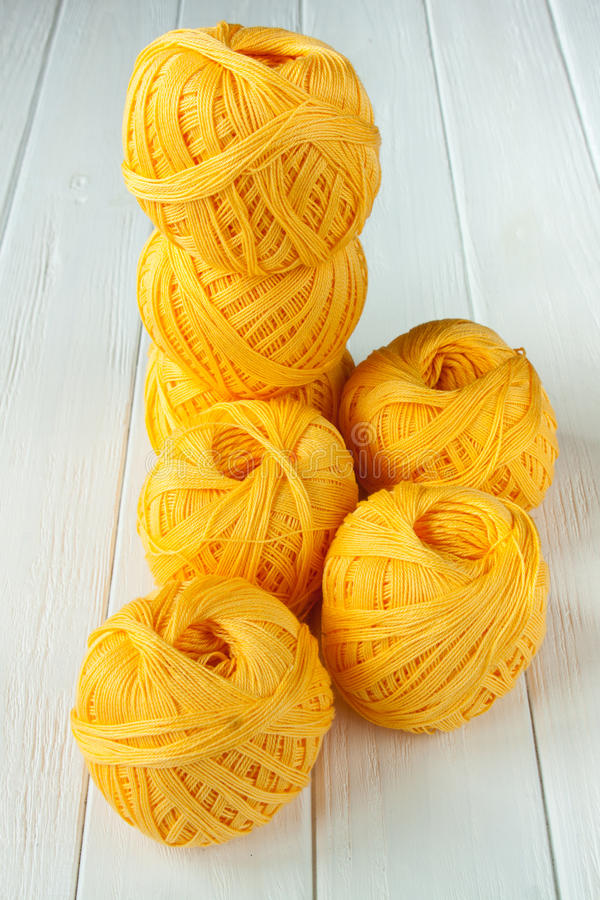 Knitting yarn rolled into balls. On a white wooden background stock photos