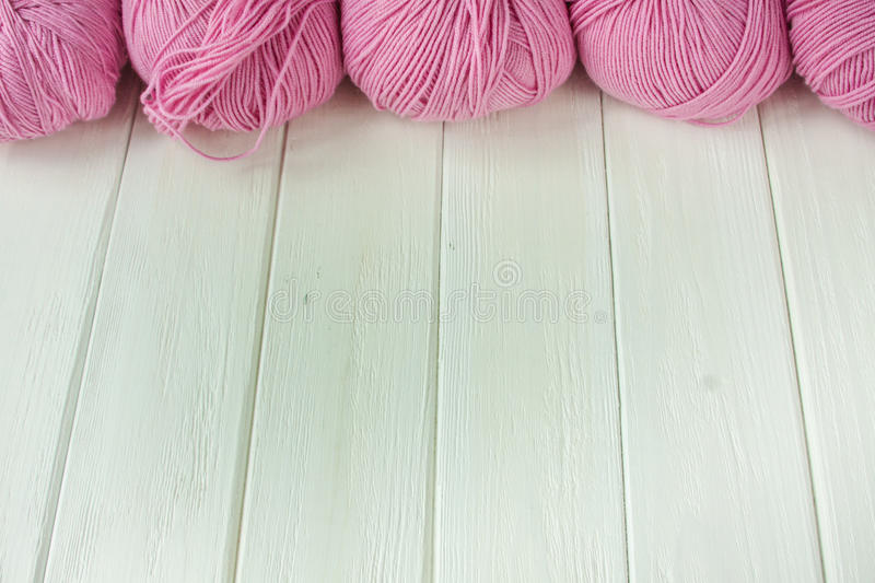Knitting yarn rolled into balls. On a white wooden background stock images