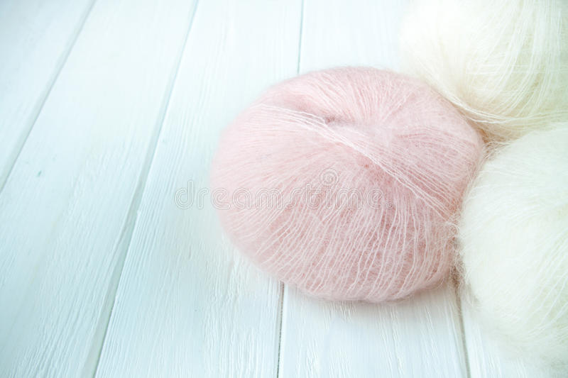 Knitting yarn rolled into balls. On a white wooden background royalty free stock images